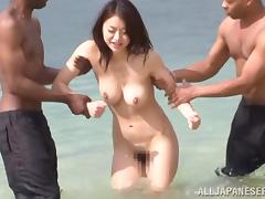 Kaede Niiyama gets naughty with two black studs on a beach