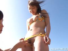 Japanese babe in a bikini rides a dick on a beach